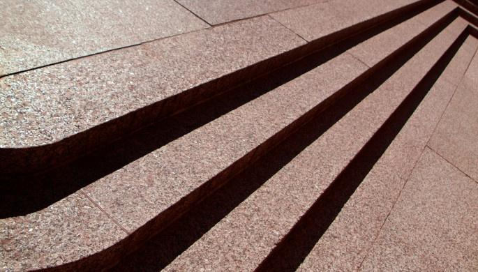 A low sun casts dramatic shadows on three pink stone steps.